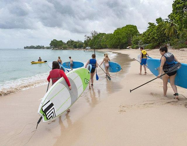 Walking on the beach with surfboards in Barbados ()