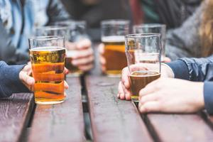 Hands holding pints at a london pub ()