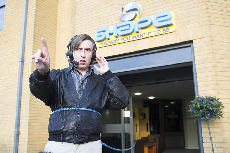 Alan Partridge standing out side Shape FM wearing a headset ()