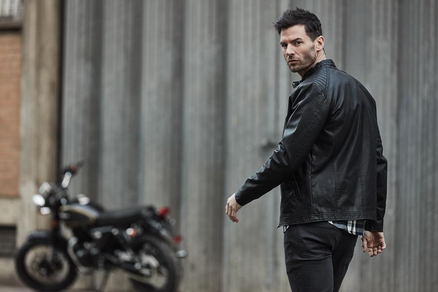 Gareth Seddon modelling a leather jacket with a vintage motor bike in the background ()
