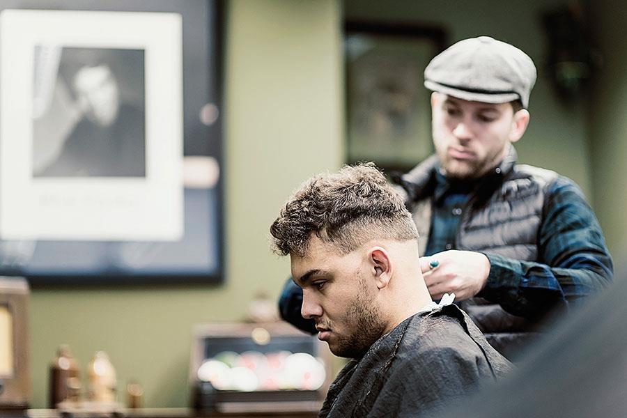 Rocket Barbers in peckham. Barber combing hair in FS magazine shoot ()
