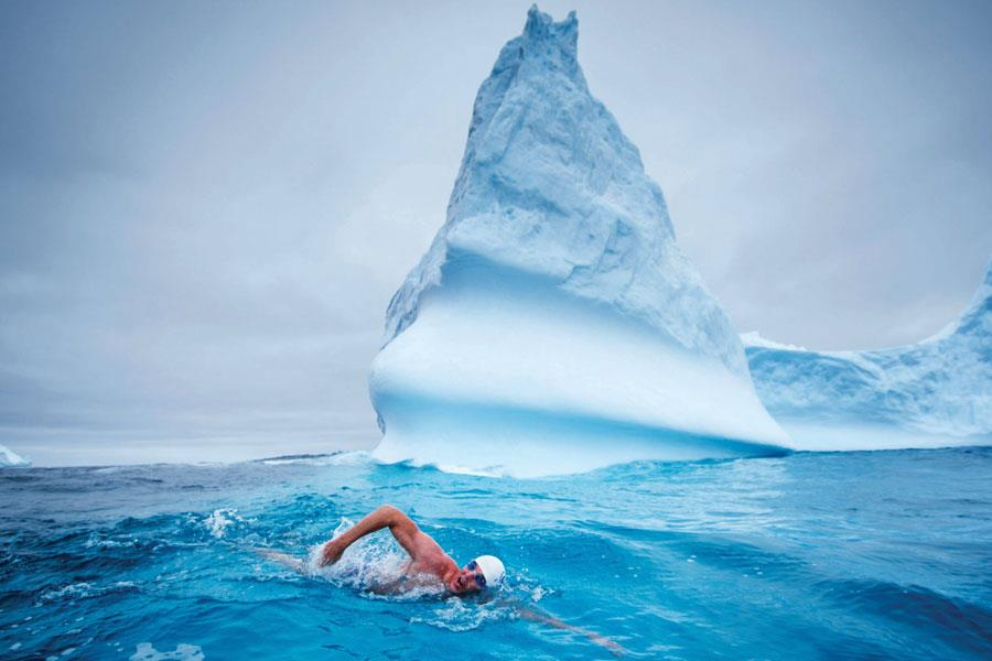 Lewis Pugh swimming past an iceberg ()
