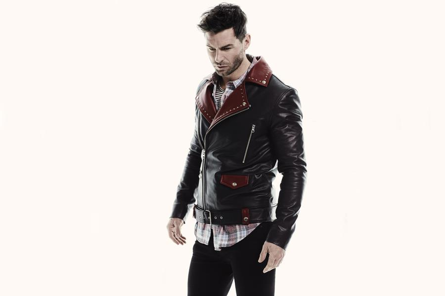 Gareth Seddon modelling a leather jacket and plaid shirt ()