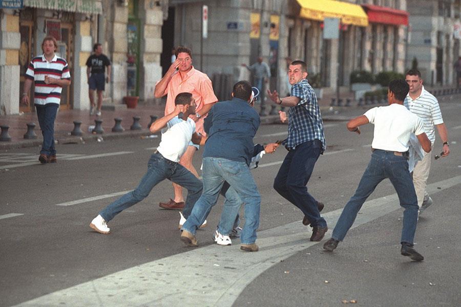 Men fighting in street ()