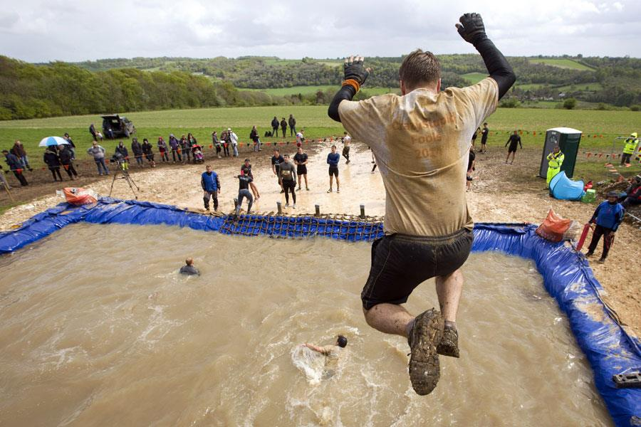 Jumping into muddy water in an obstacle race  ()